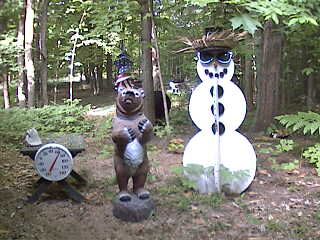 A real black bear is in the background between the snowman and the fake bear. Can you see it?