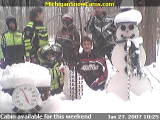Gordon, Stephanie, Bradley, Justin, Marie, Trenton and Randy standing knee deep in snow next to the Snowman.