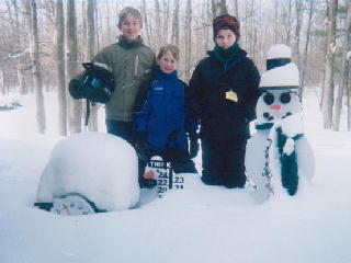 Matt and Jack Funk with Tyler Bettelon standing next to the snowman.