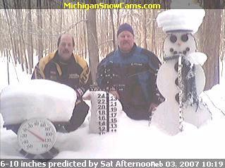 Chet Parisotto and Tom Wyatt kneeling next to the Snowman.